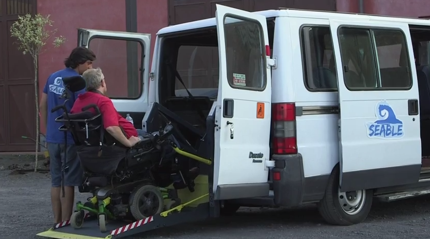 a man in a wheelchair is being helped into a mobility car. mobility cars make it easier for disabled people to drive to accessible city breaks