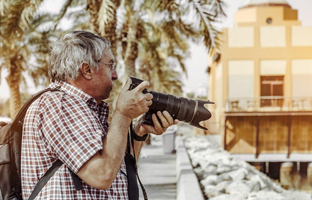 elderly man taking a photograph